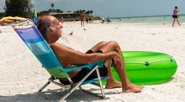 Man sitting on beach on lawn chain in Sarasota, Florida